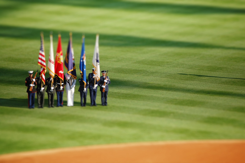 Holding flags during the national anthem tilt Shift Photography